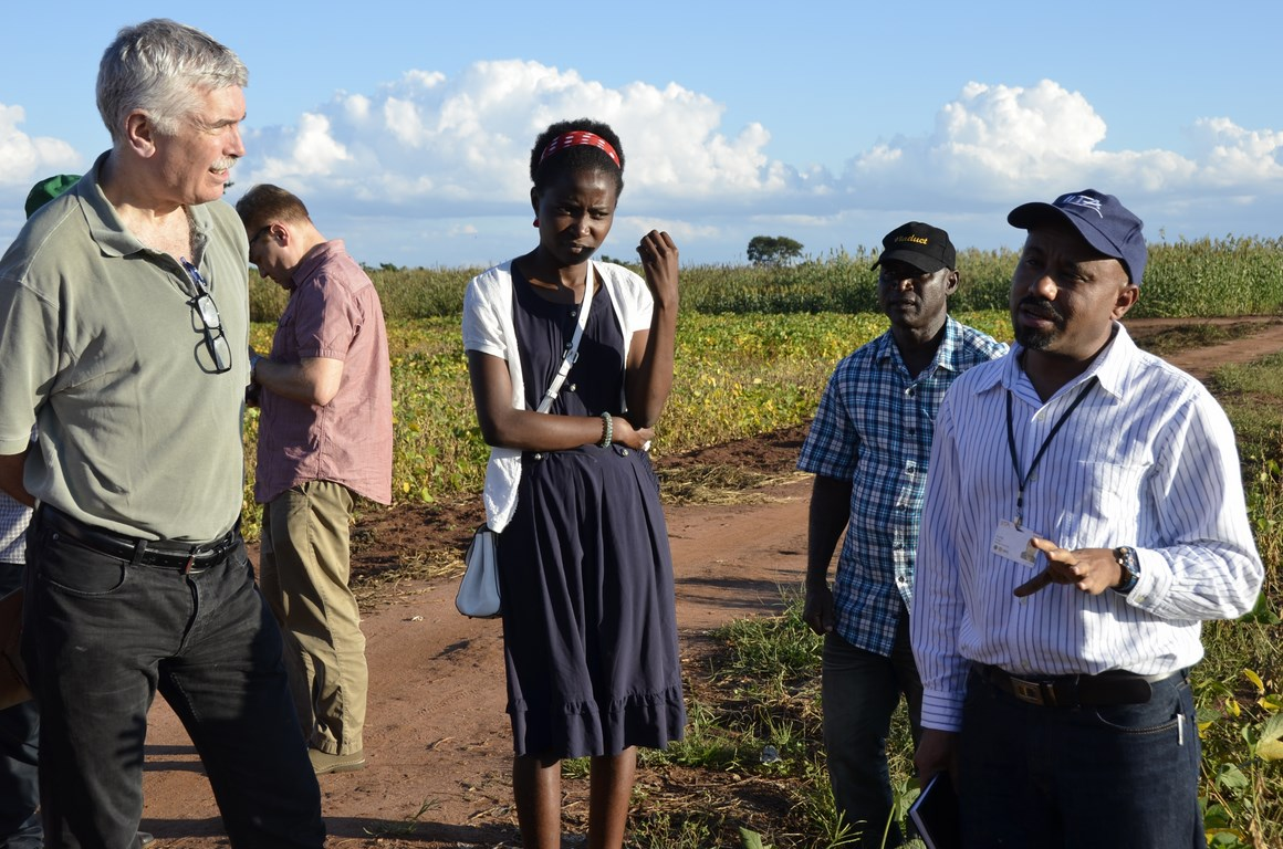 Dr Rob Bertram (left) listening to a presentation by Dr Alene Arega of IITA on a soy demonstration field.