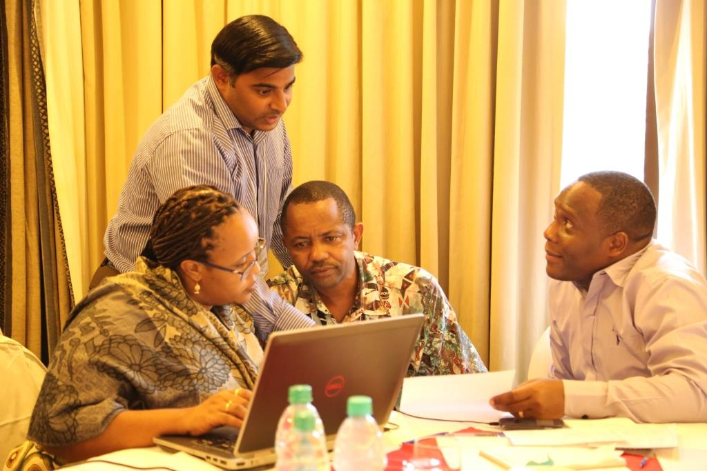 L-R: Gaudiose Mujawamariya and Kalimuthu Senthilkumar (AfricaRice), Elisha Mkandya (ILONGA Agricultural Research Institute), and Silvanus Mruma (NAFAKA) discuss the proposed work plan for the rice team's year 2 activities (Photo credit: IITA/Gloriana Ndibalema).