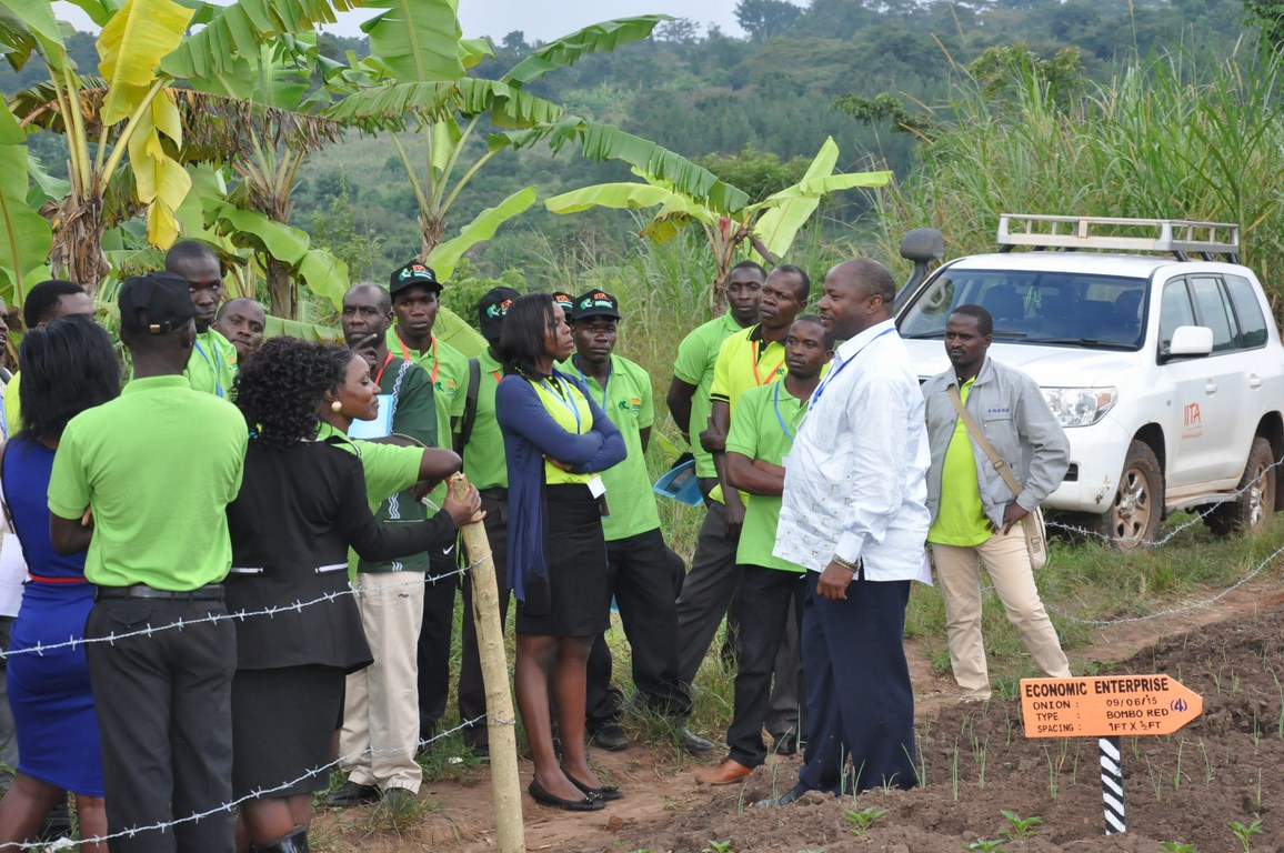 IITA DG speaking to one of the Uganda youth Agripreneurs during a field visit to see some of the farming activities they are already engaged in.
