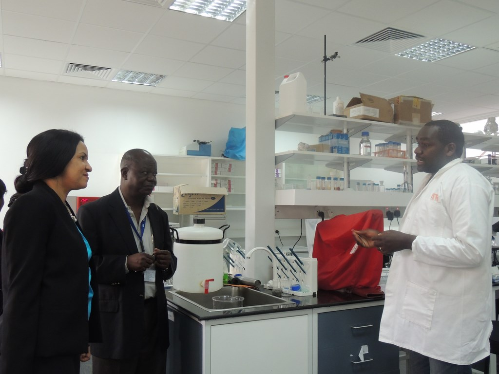 Dr Tausi Kida listens to Mr Harun Murithi's (right) explanation about research on soybean rust. She is accompanied by Dr Victor Manyong (center).