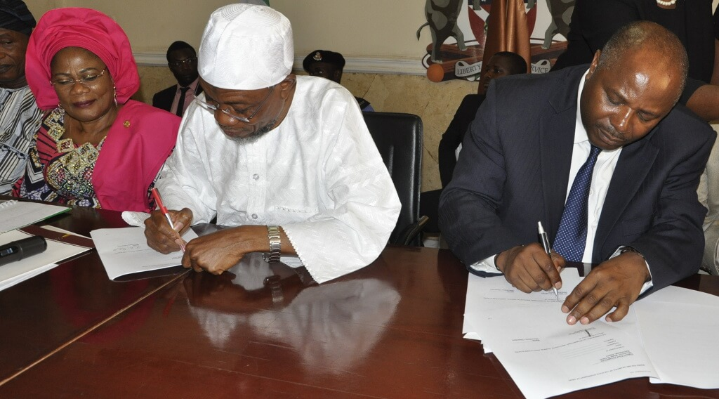 Picture of Gov. Aregbesola and DG Sanginga sign the MoU while Otunba Grace Titilayo Laoye-Tomori, Deputy Governor, Osun State, looks on.