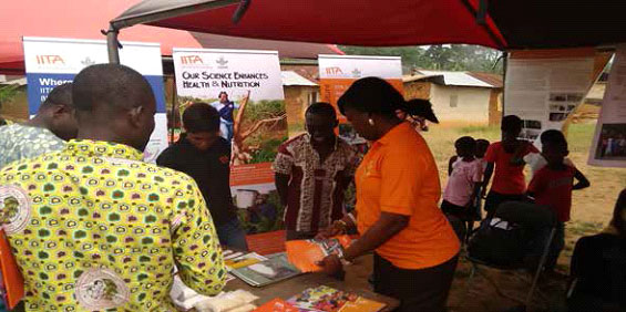 Cassava Breeder Elizabeth Parkes attending to farmers and guests at the IITA stand.